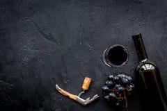 Öppna vinet Near flaska för korkskruv på svart copyspace för bästa sikt för bakgrund arkivbilder