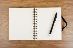 Öppnad anteckningsbok med den svarta elastiska musikbandet och blyertspennan Arkivbild