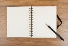 Öppnad anteckningsbok med den svarta elastiska musikbandet och blyertspennan Arkivfoton