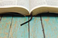 Öppnad bibel med en bokmärke på trä Royaltyfria Bilder