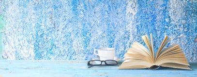 Öppnad bok, kopp kaffe Arkivfoto
