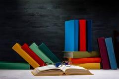 Öppnad bok med exponeringsglas och en andra färgrika böcker Fotografering för Bildbyråer