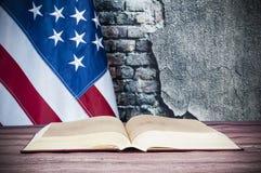 Öppnad bok på en bakgrund av USA flaggan Arkivbild