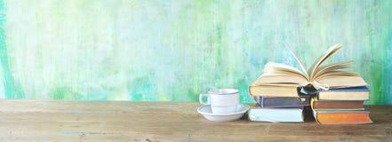 Öppnad bok på en hög av böcker och en kopp kaffe, panorama arkivbilder