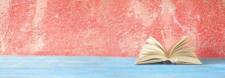 Öppnad bok på röd grungy bakgrund Arkivbilder