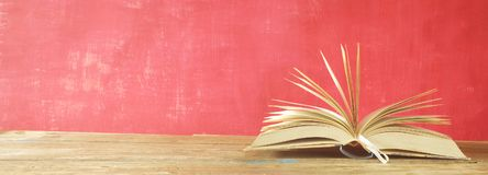 Öppnad bok på röd grungy bakgrund, panorama- bra kopieringsutrymme Royaltyfri Foto