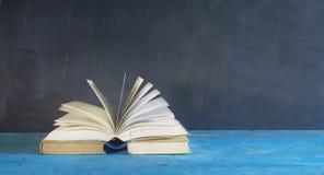 Öppnad bok på svart grungy bakgrund, Royaltyfri Foto