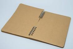 Öppnad bruntslättanteckningsbok med vit bakgrund och den selektiva fokusen Royaltyfria Bilder