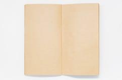 Öppnad bruntslättanteckningsbok på vit bakgrund och selektiv fokus Arkivfoton