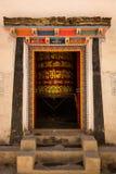 Öppnad färgrik dörr med det buddistiska be instrumentet inom rummet med forntida skrifter på det Royaltyfri Bild