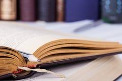 Öppnad gammal bok med den gråa blyertspennan och flera böcker Fotografering för Bildbyråer