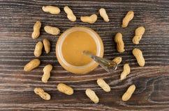 Öppnad krus med jordnötsmör och tesked och spridda jordnötter Arkivfoto