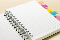 Öppnad liten anmärkningsbok med den färgglade klistermärken Arkivfoton
