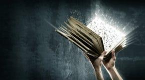 Öppnad magisk bok med magiska ljus Arkivbild