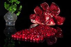Öppnad mogen granatäpple reflekterad på svart Royaltyfria Foton