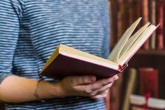 Öppnad röd bok i händerna av en flicka slapp fokus arkivbild