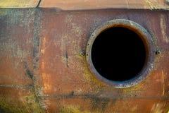 Öppnad rostig manhål på orange bränslebehållare Arkivfoton