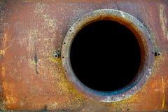 Öppnad rostig manhål på orange bränslebehållare arkivbild