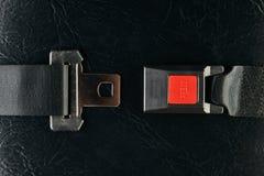 Öppnad säkerhetsbälte på svart läderbakgrund Royaltyfri Bild