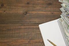 Öppnad spiral Notepad, dollarkassa, Pen On Wood Table Backgroun Arkivbilder