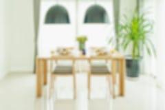 Öppnad vit dörr till den trääta middag tabellen och stolar med den eleganta tabellinställningen Fotografering för Bildbyråer