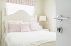 Öppnad vit dörr till det lyxiga sovrummet med kuddar och skrivbordlampan Royaltyfria Bilder