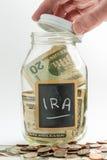 Öppnande glass krus för hand som används för IRA fonden royaltyfria bilder