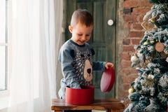 Öppnande julklapp för ung pojke framme av julgranen arkivbild