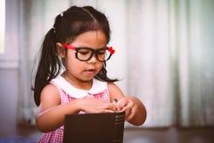 Öppnar den asiatiska lilla flickan för barnet en bok Royaltyfri Foto