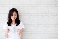 Öppnar den lyckliga unga asiatiska kvinnan för den härliga ståenden boken med cement- eller betongbakgrund royaltyfri bild