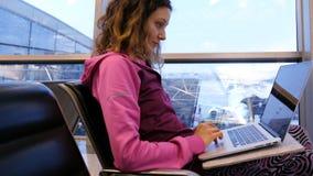 Öppnar den turist- freelanceren för kvinnan en bärbar dator, och tryck, väntar på en nivå och ett flyg på flygplatsen, i det vänt royaltyfri fotografi
