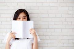 Öppnar det lyckliga nederlaget för härlig kvinna för stående ung asiatisk bakom boken med cement- eller betongbakgrund royaltyfria bilder