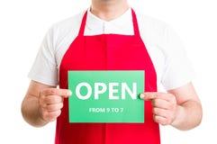 Öppnar det manliga anställdinnehavet för supermarket tecken 9 till 7 Royaltyfri Bild