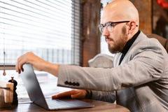 Öppnar locket av bärbara datorn och maskinskrivningen på tangentbordet som pratar Den unga mannen underhåller en blogg lyckat fol royaltyfri bild