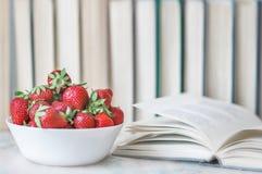 Öppnar röda jordgubbar för ny sommar i ett vitt lock och boken på skrivbordet på bakgrund med böcker Begreppet av sund mat och ed arkivbilder