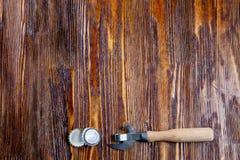 Öppnare och lock från öl på en trätabell Ram Frigör stället Royaltyfri Bild