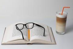 Öppnat bok och exponeringsglas av Latte Macchiato Royaltyfri Bild