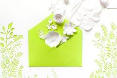 Öppnat hantverkpapperskuvert mycket av vårblomningsakura pappers- blommor på vit bakgrund Royaltyfria Foton