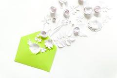 Öppnat hantverkpapperskuvert mycket av vårblomningsakura pappers- blommor på vit bakgrund Top beskådar Begrepp av förälskelse Royaltyfri Bild