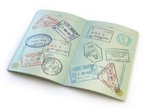 Öppnat pass med visumstämplar på sidorna på vit Arkivbild