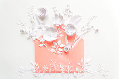 Öppnat rosa kuvert mycket av variosvitbokblommor på vit bakgrund Fotografering för Bildbyråer