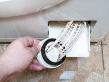Öppning av filtret av den gamla tvättmaskinen arkivfoton