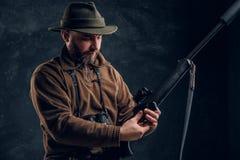 Öppning av vårjaktsäsongen Jägare som är klar att jaga och ladda ett jaga gevär Studiofoto mot ett mörker arkivfoto