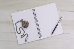 Öppning för bok för anmärkning för vit sida för mellanrum tom med penn- och tappningrovan på den gråa trätabellen genom att använ fotografering för bildbyråer