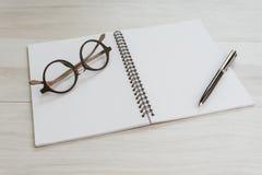 Öppning för bok för anmärkning för vit sida för mellanrum tom med pennan och glasögon på den gråa trätabellen genom att använda s arkivbild
