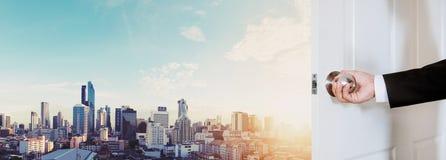 Öppning för knopp för dörr för affärsmanhand hållande, med Bangkok cityscape i soluppgång royaltyfri bild