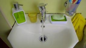 Öppning för vattenkran för kran för vattenklapp och stänga sig vid en hand för person` s i badrummet arkivfilmer