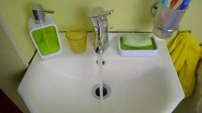 Öppning för vattenkran för kran för vattenklapp och stänga sig vid en hand för person` s i badrummet stock video