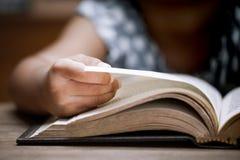 Öppning och läsning för Closeupbarnhand en bok i arkiv royaltyfri fotografi
