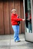 Öppningsdörr för äldre dam royaltyfri foto